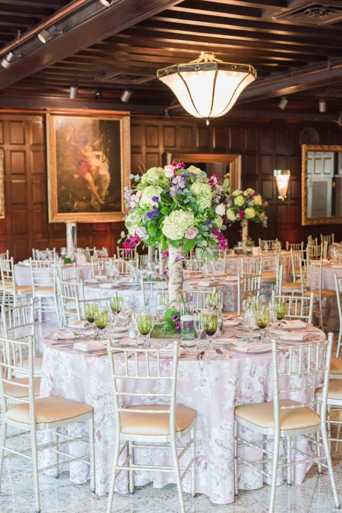 shot of tall table arrangement with birch wood stalk topped with greenery, lavender and cream roses, pale green hydrangeas, fuschia orchids on top of pale floral table linens