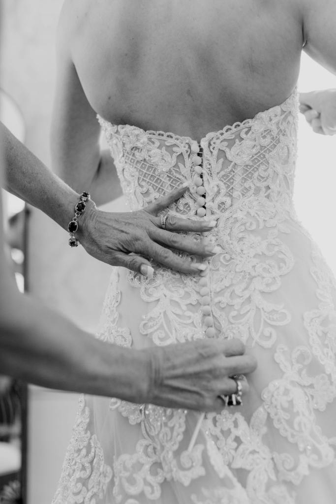 black and white photo of the back of the brides gown as its being buttoned up