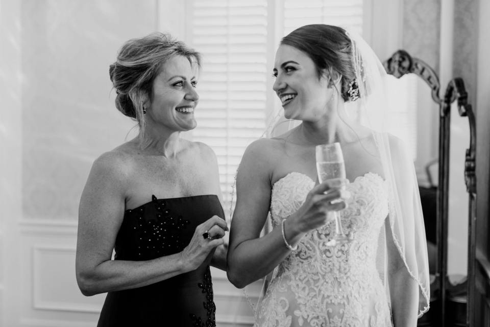 black and white candid photo of bride and her mother enjoying champagne