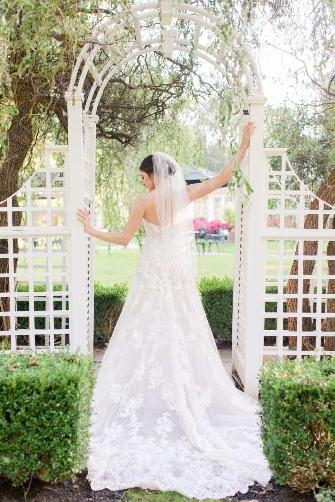 full length bridal portrait of back of bride and dress under trellis at Shadowbrook at Shrewsbury