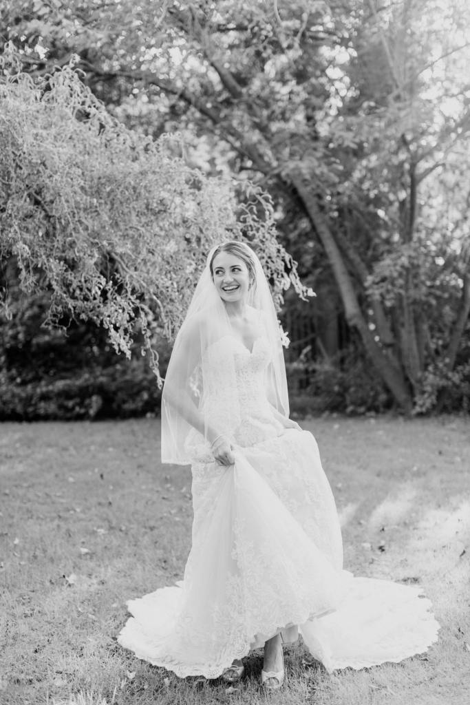 black and white candid photo of bride dancing under trees