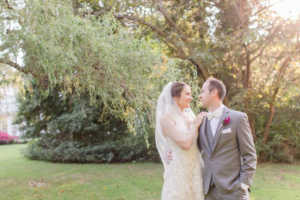 bride and groom gazing at one another under trees within a garden at Shadowbrook at Shrewsbury