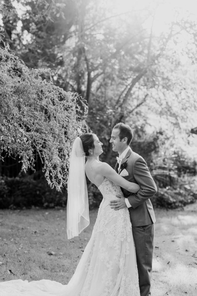 black and white candid photo of bride and groom in garden