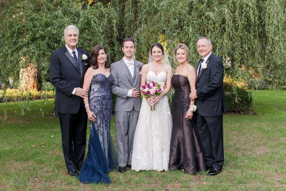 formal photo of bride and groom and both of their parents under tree