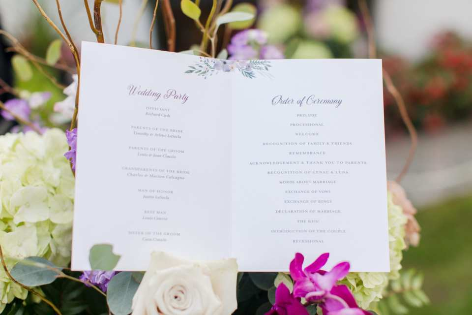 white with purple calligraphy ceremony program on ceremony florals