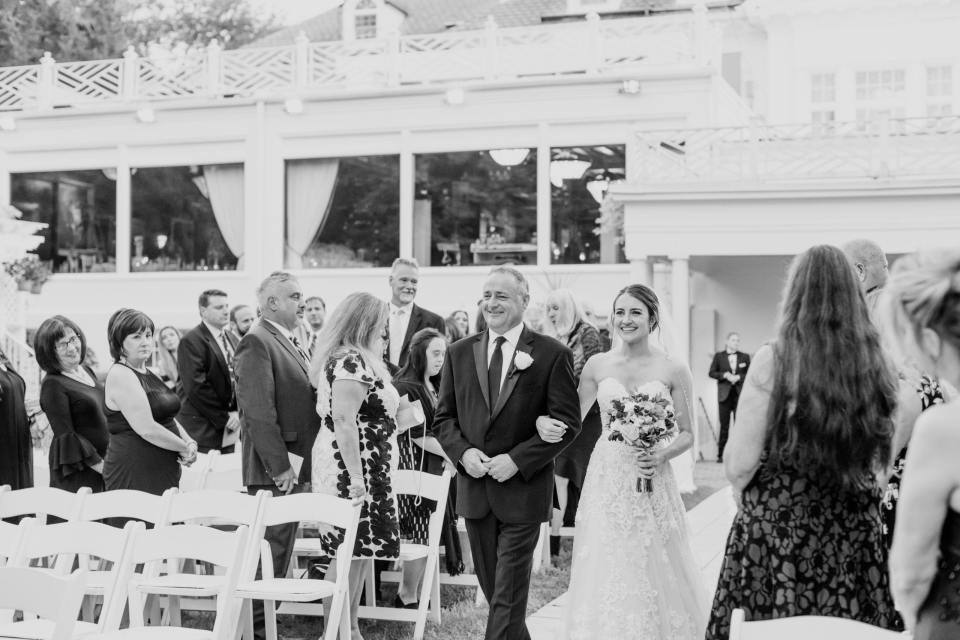 black and white photo of bride walking down the aisle with her father