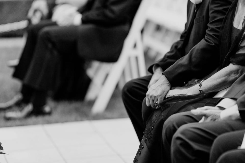 a black and white photo of a couple sitting in the guests chairs holding hands while listening to the wedding ceremony
