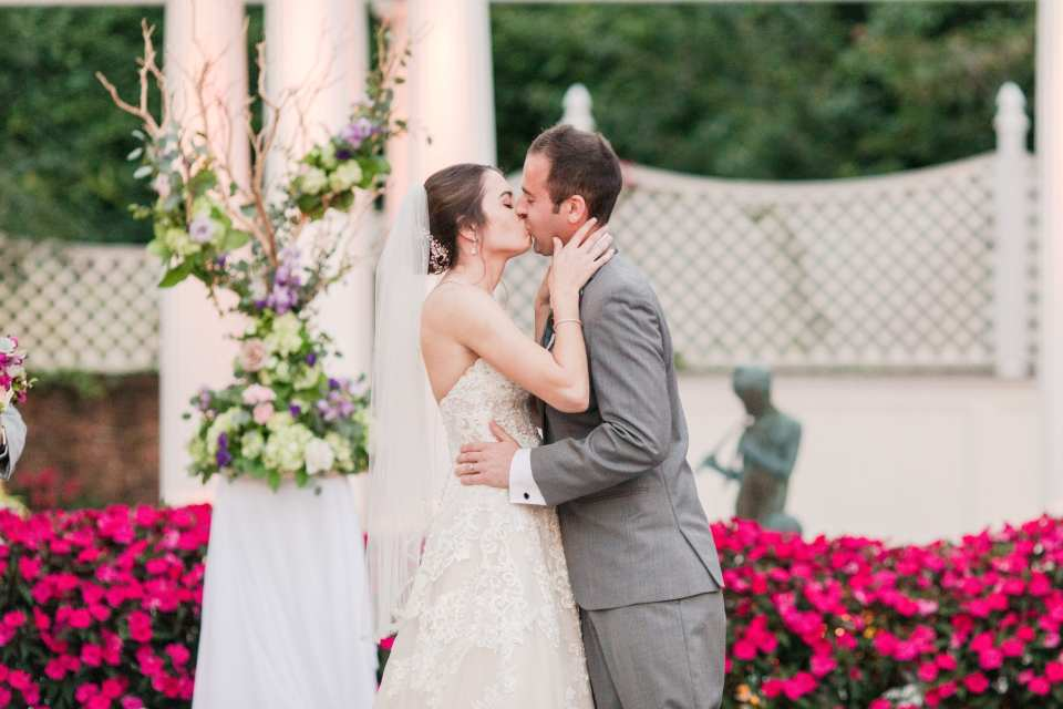 the bride and groom take their first kiss as husband and wife at the end of the wedding ceremony in front of the colorful garden background and wedding ceremony flower arrangements