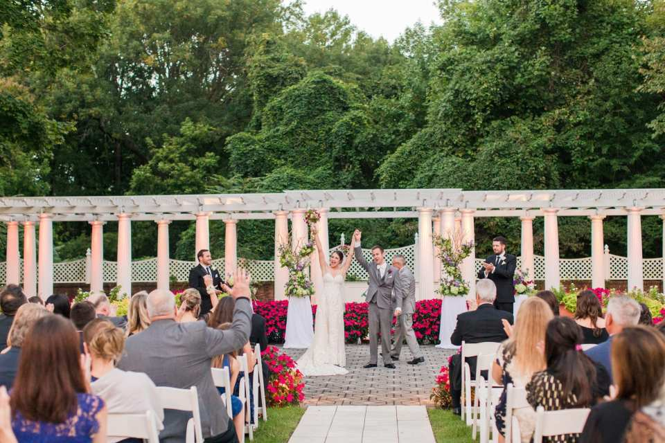 a wide photo of the married couple being introduced as husband and wife, celebrating with their arms in the air, against the white trellis and pink floral garden backdrop