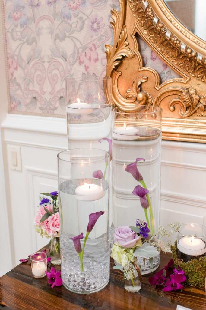 accent decor inside Shadowbrook at Shrewsbury consisting of three clear glass water filled cylinder vases with floating candles and purple lilies. The entire arrangement is surrounded by candles and other florals made from the ceremony florals