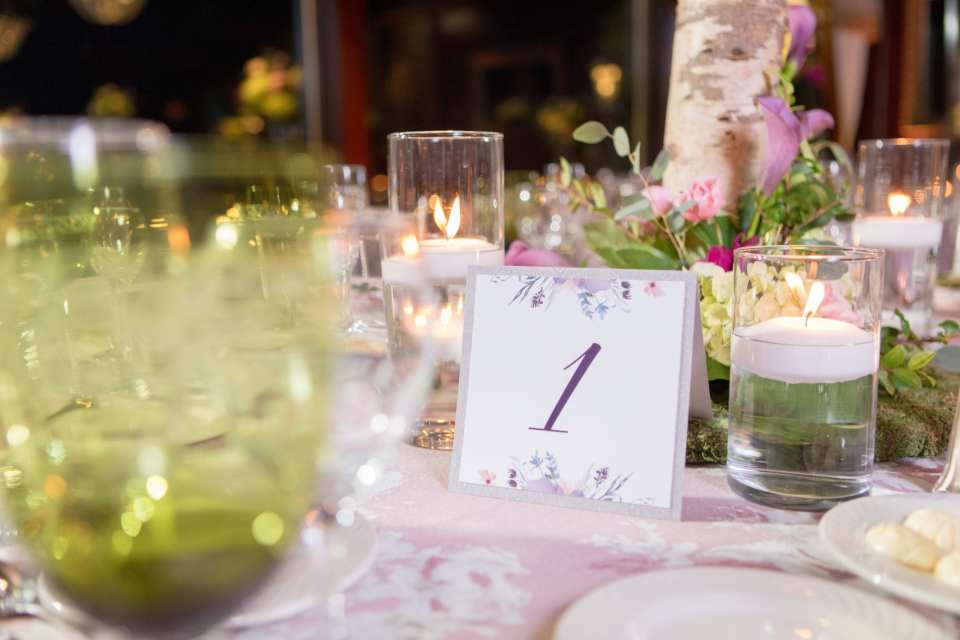 close up of table number 1 with green classware, candles, floral table linen