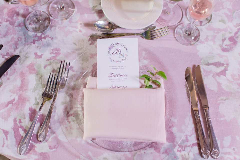 menu written with purple calligraphy wrapped in light lavender pink napkin on a clear charger with a greenery accent, all against floral table linen