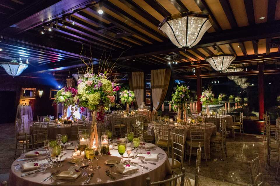 wide shot of reception room with tables covered with floral print linens, off white chivari chairs, green glassware, and tall table arrangement with birch wood stalk topped with greenery, lavender and cream roses, pale green hydrangeas, fuschia orchids