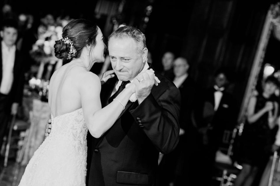 black and white photo of bride dancing with her emotional father