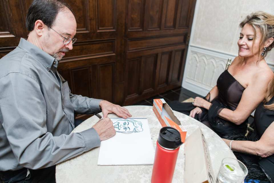 candid photo of caricature artist drawing during wedding reception