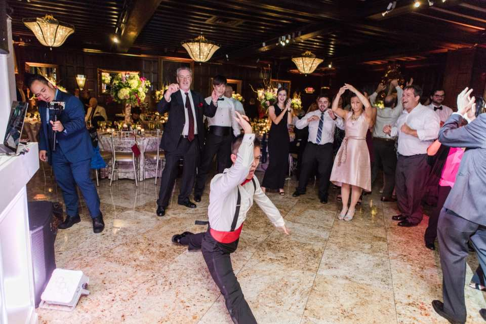 guests dancing and cheering man doing split during wedding reception