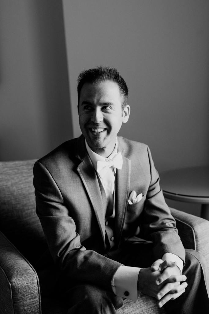 black and white candid photo of groom sitting