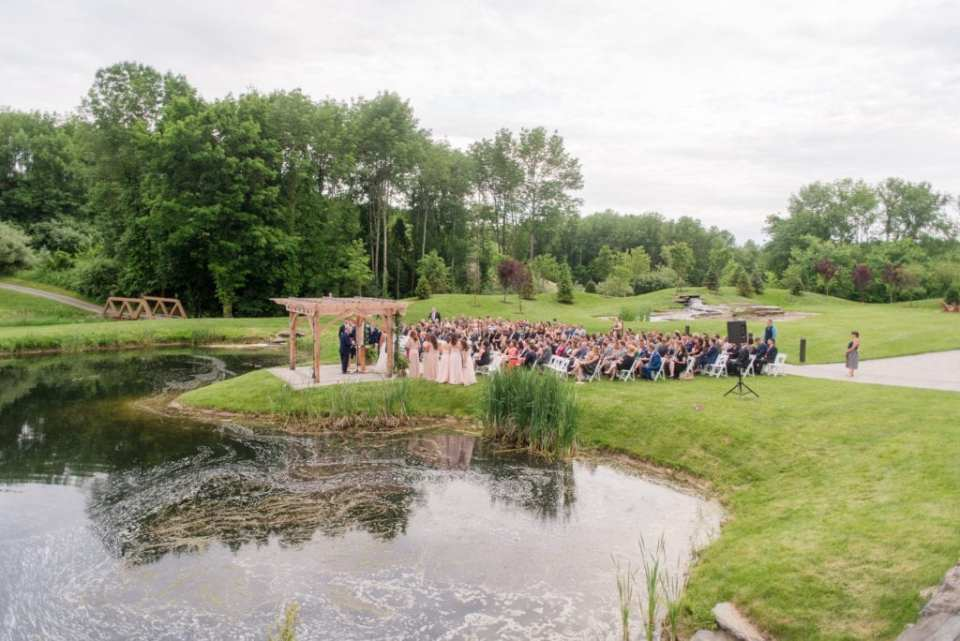 View of ceremony area from above at Bear Brook Valley, featuring views of bridge, water, and waterfall