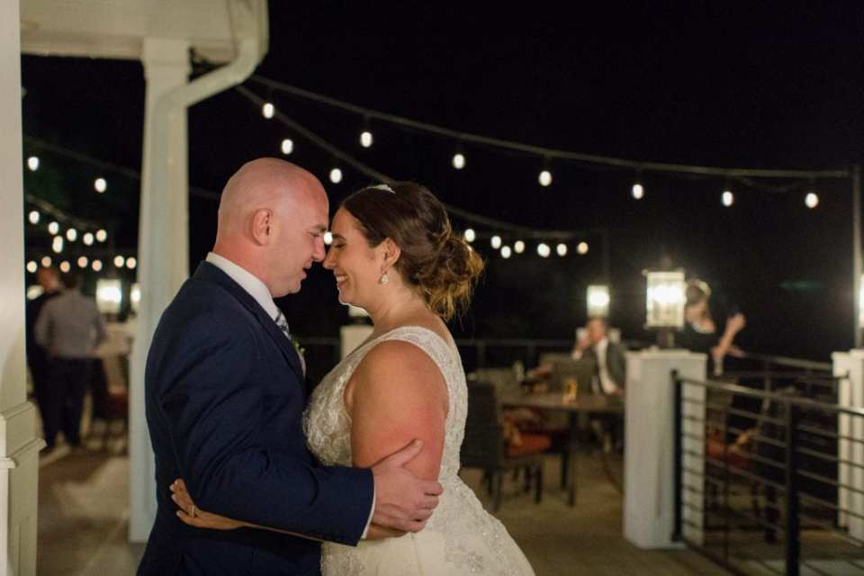 Photo of bride and groom on Bear Brook Valley porch at night showing their bistro lights