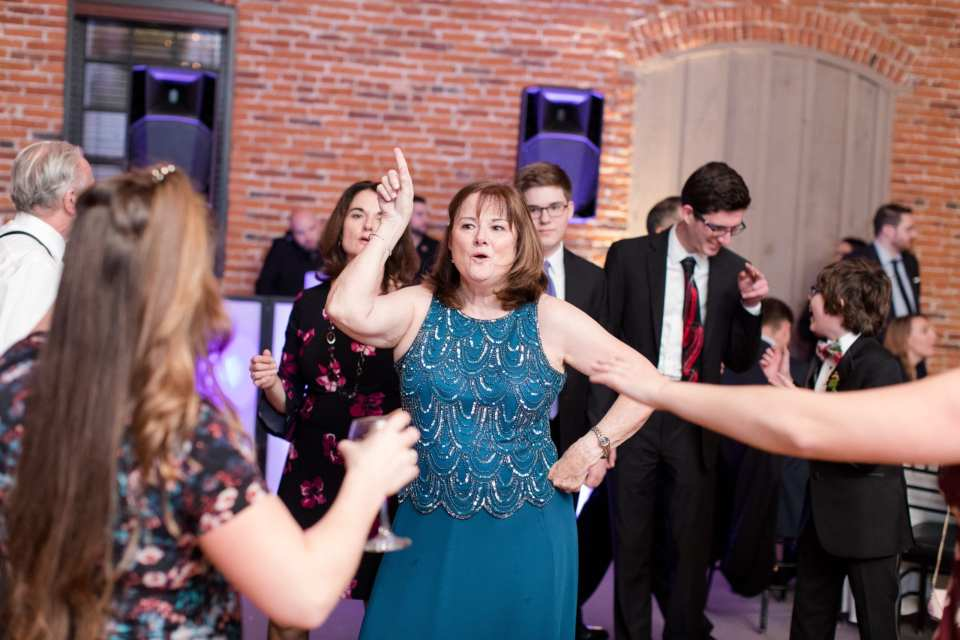 guest in blue teal gown dancing disco style during reception