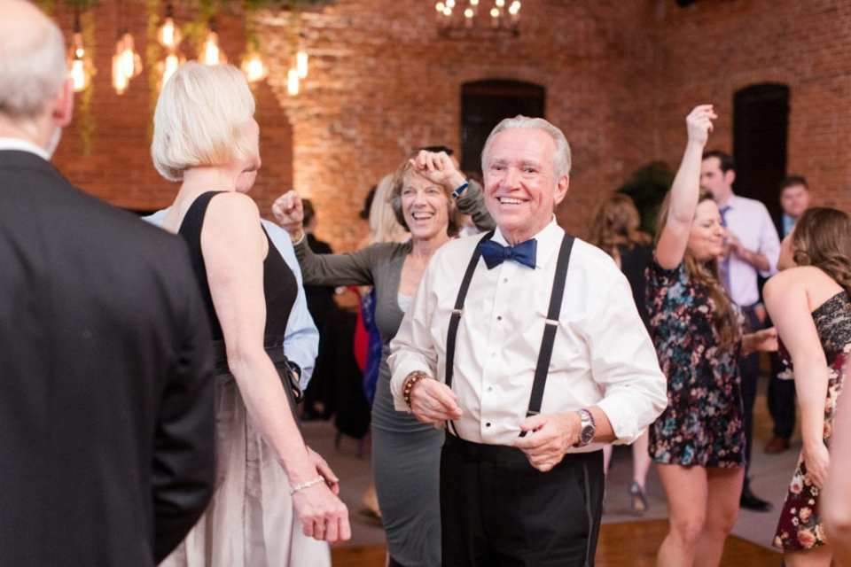father of the groom in black suspenders and navy blue bow tie dancing during reception