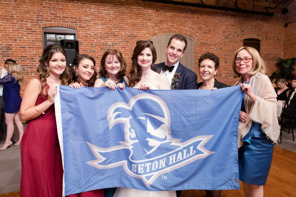 bride and groom with seton hall flag and fellow alumni