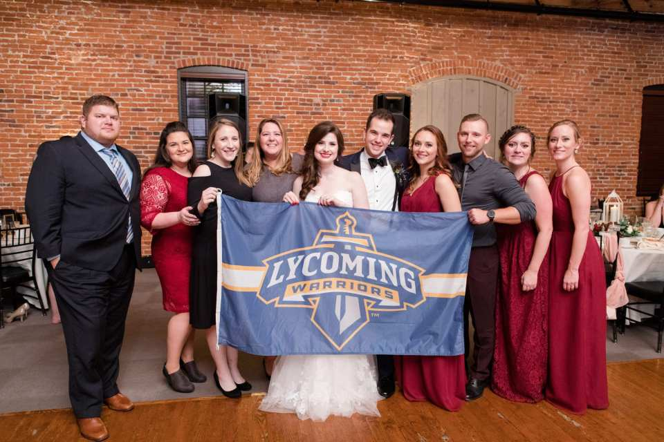 bride and groom posing with Lycoming Warriors flag with fellow alumni