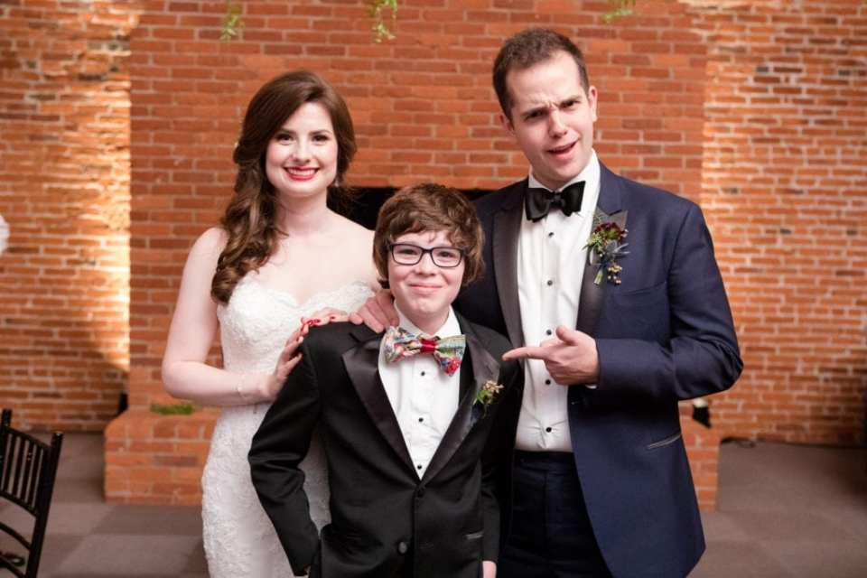 bride and groom with young guest in comic book bow tie
