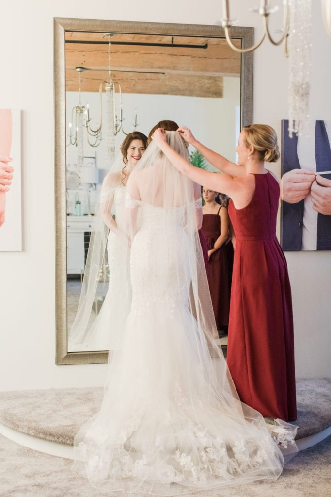 bride standing in front of full length wall mirror as her veil is adjusted by bridal party