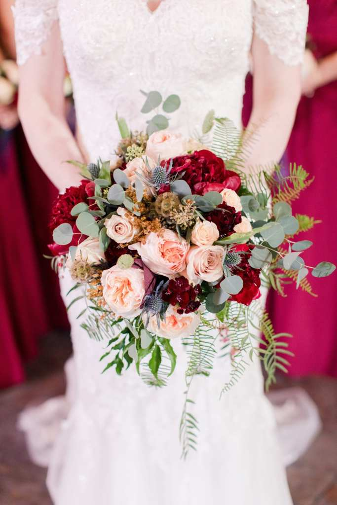 close up of bridal bouquet of red and cream roses, dark red and blush peonies and greens being held by bride
