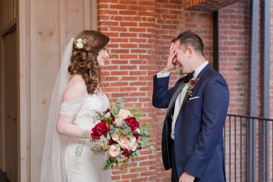 bride smiling lovingly at her groom who is in tears during their first look