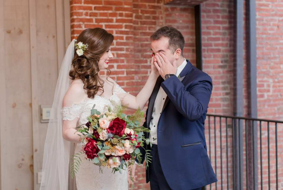 bride helping groom wipe away tears during first look