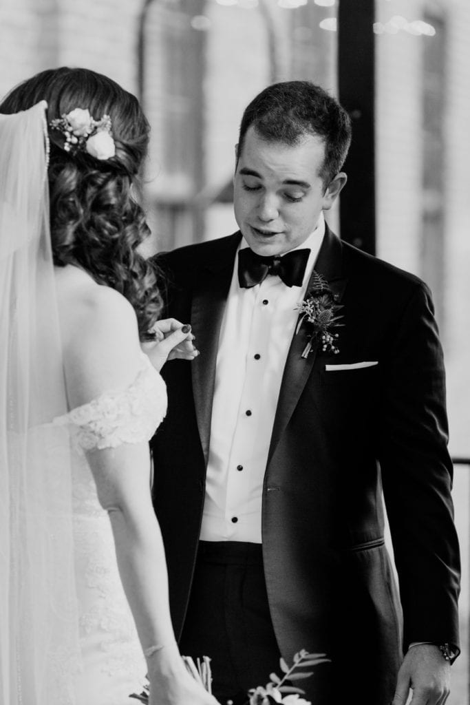 black and white photo of groom looking at his bride during first look