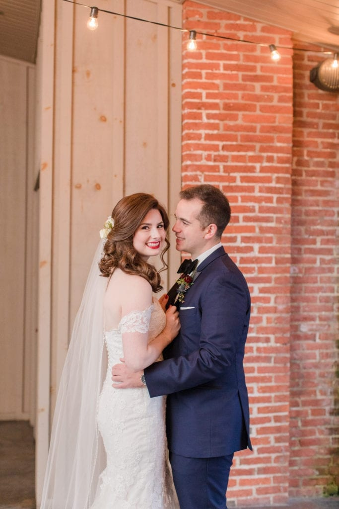 photo of bride and groom in front of brick and wood wall under cafe lights