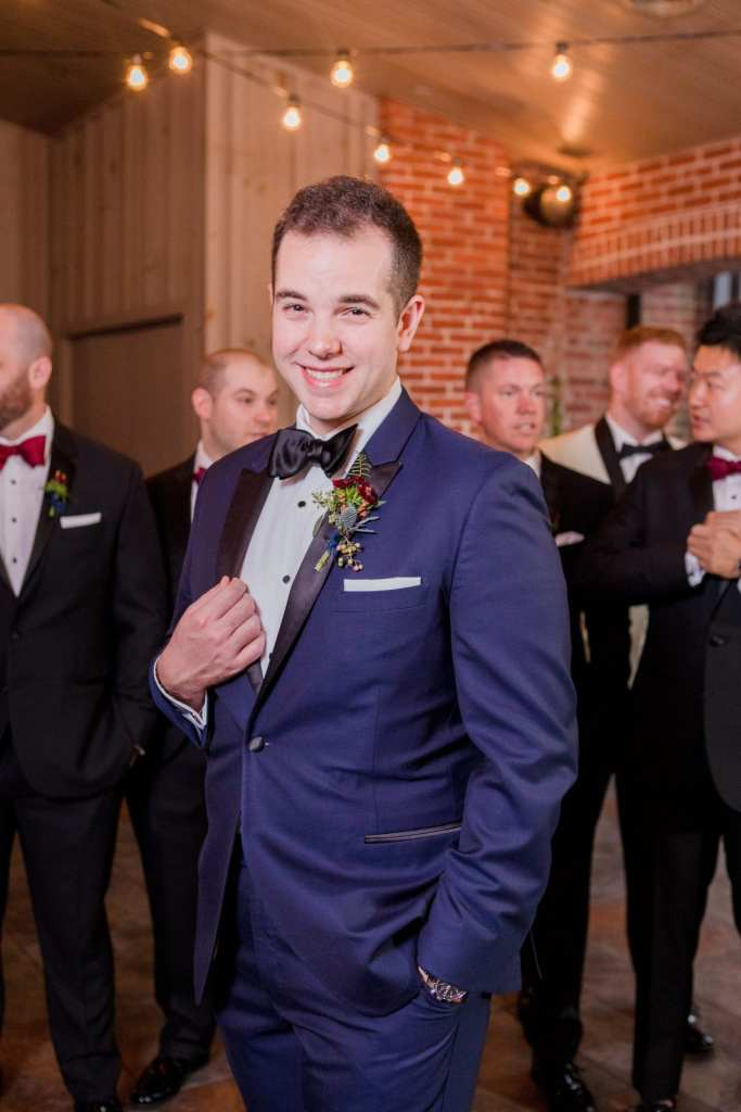 groom in navy blue and black tuxedo posing in front of his groomsmen