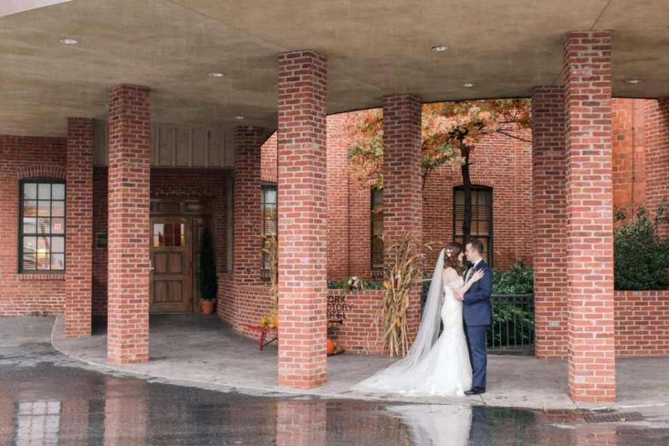 bride and groom portrait looking at each other in between brick pillars outside the Cork Factory Hotel