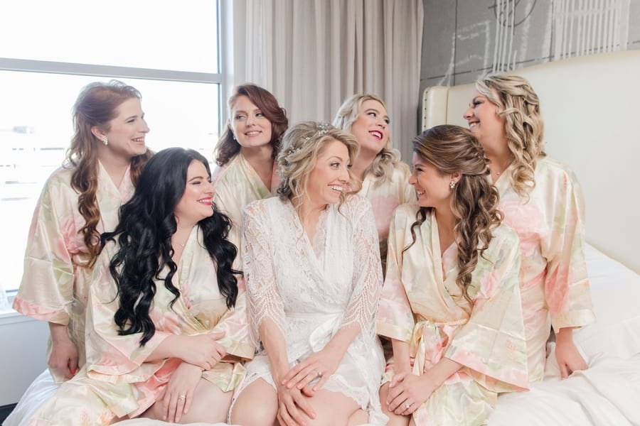 bride in a white robe sitting on the bed in a light filled hotel room surrounded by her bridal party in coordinating floral silk robes