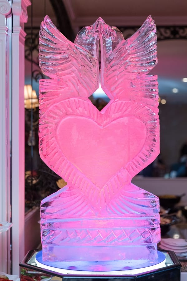 ice sculpture of kissing doves on a heart with pink uplighting