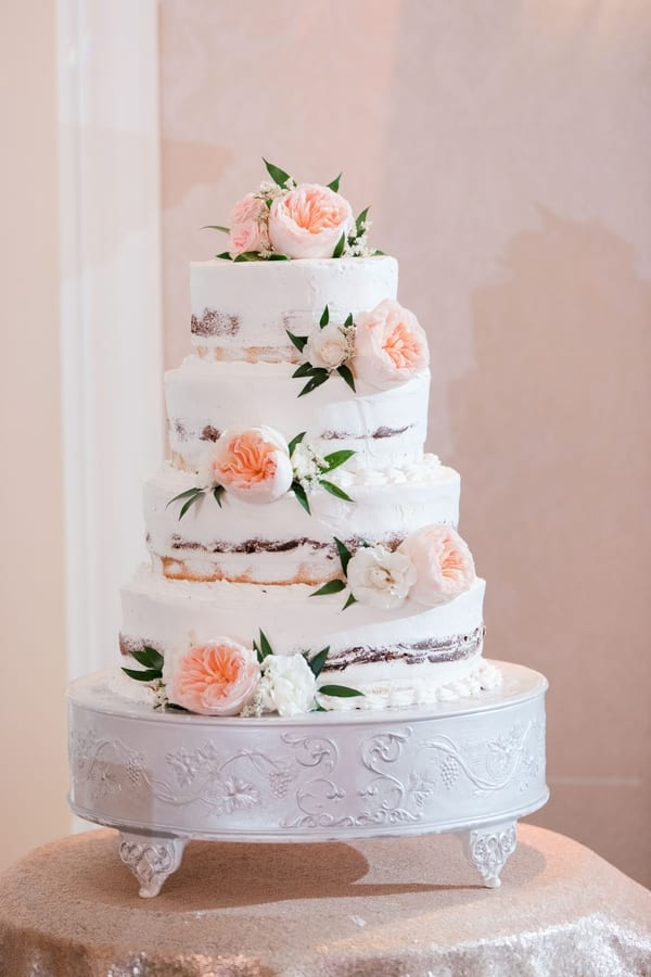 four tier semi naked wedding cake with blush florals on display on a white cake stand