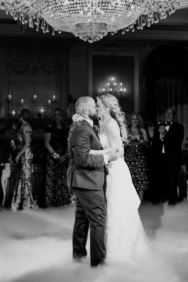 black and white photo of bride and groom dancing in fog