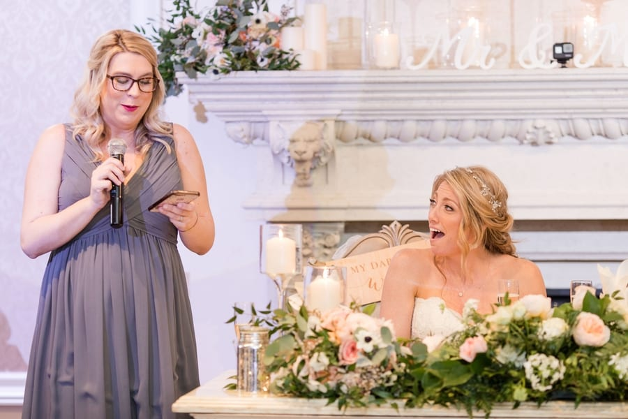 maid of honor giving her speech while bride looks on, gasping