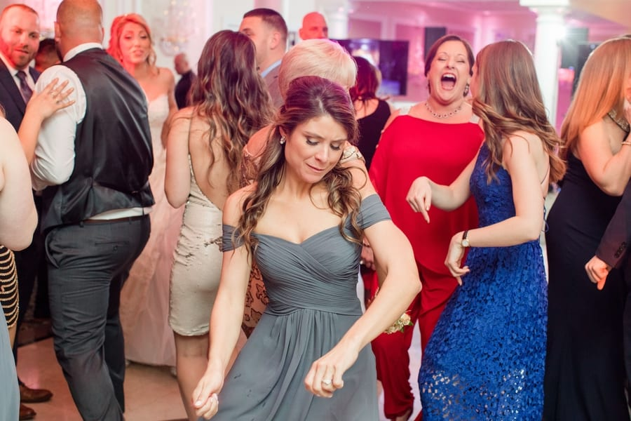 member of the bridal party in a grey gown dancing during the reception
