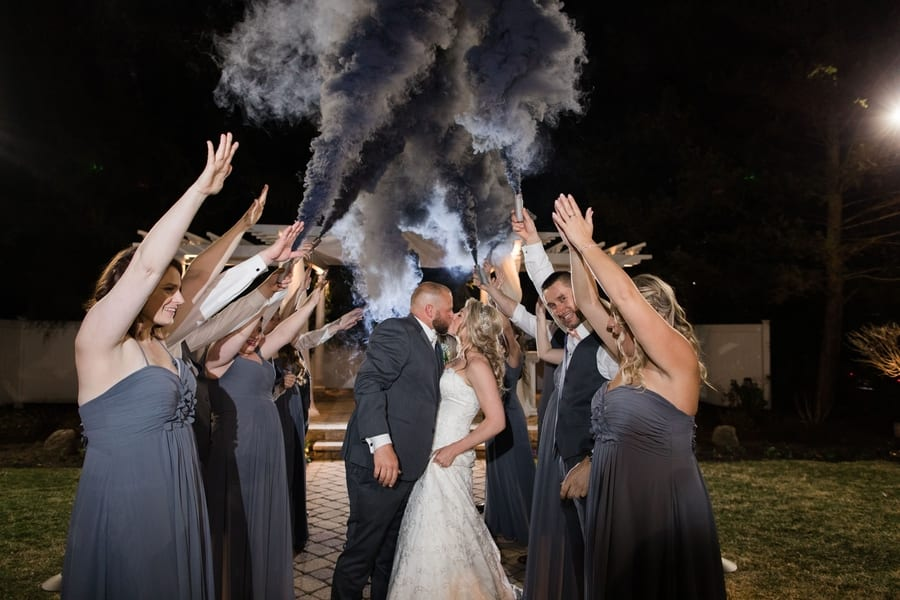 bride and groom kissing under smoke bomb tunnel of the wedding party
