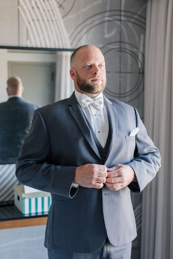 groom buttoning his grey tuxedo jacket