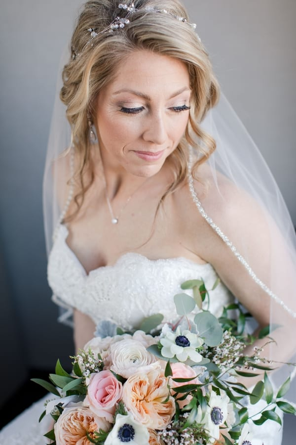 3/4 shot of bride sitting holding her bridal bouquet at her waist