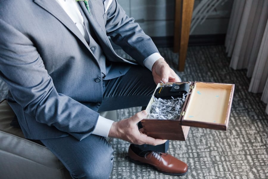 3/4 shot of groom sitting down when opening the wooden box containing his personalized Leatherman tool