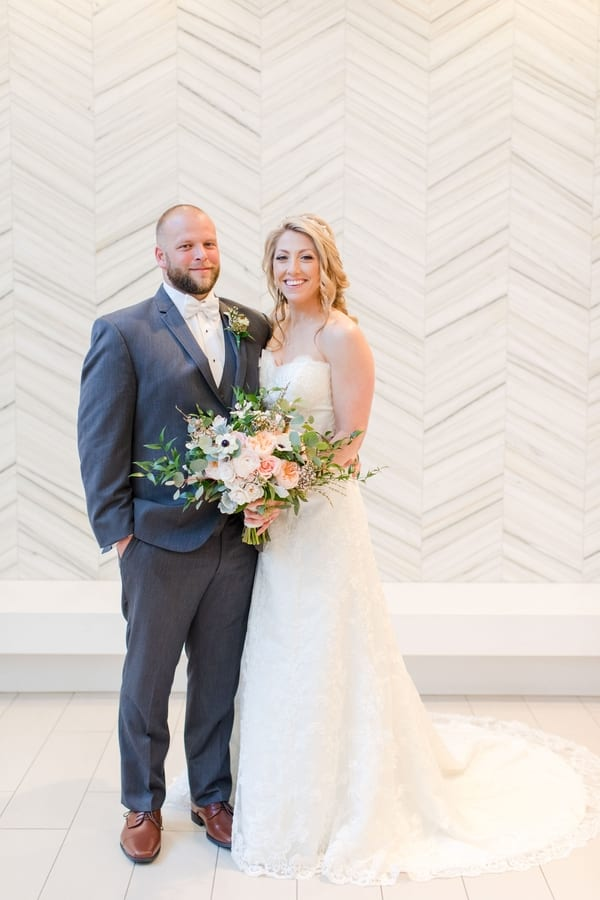 full length formal bride and groom portrait in front of white patterned wall