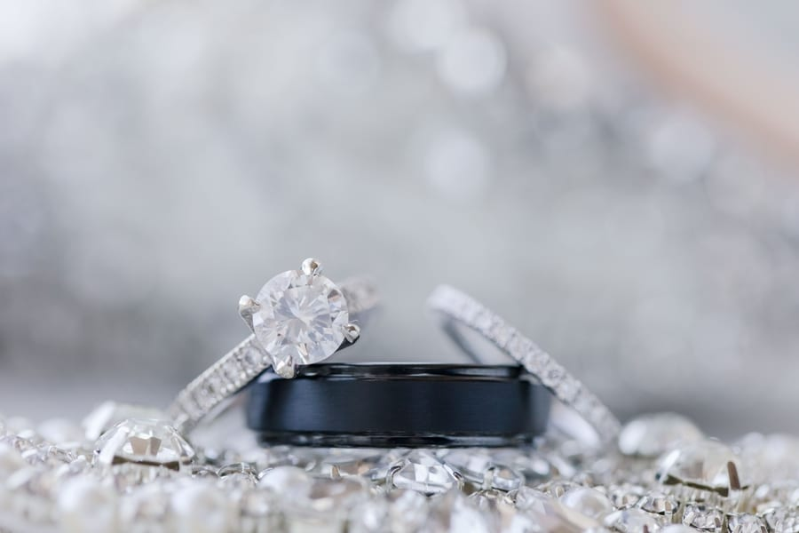 close up photo of brides round diamond engagement ring with channel set band, grooms black wedding band, and brides diamond eternity wedding band