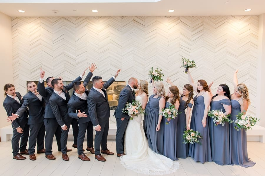 informal fun wedding party photo with bridal party on brides side, groomsmen on grooms side while bride and groom kiss