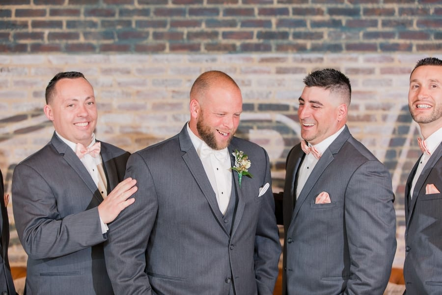 candid shot of groom in grey tuxedo with a few of his groomsmen in grey tuxedos with peach ties around him